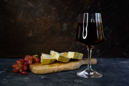 selective focus, clear glass of red grape wine. Olive wood Board with cut melon and pink grapes. Still life, low key, with copyspace Stok Fotoğraf