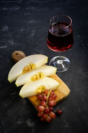 selective focus, clear glass of red grape wine. Olive wood Board with cut melon and pink grapes. Still life, low key, with copyspace 版權商用圖片