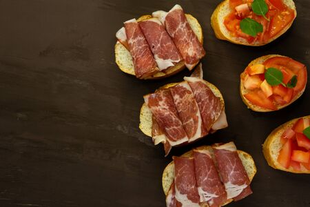 selective focus, snack bruschetta, with red tomatoes and Basil, and smoked meats. On a small white bread baguette on a dark background Stock Photo