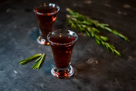 cherry, berry tincture on a dark background, with a sprig of rosemary