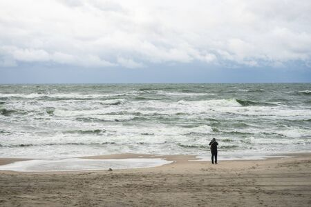 selective focus, the Baltic sea and a man on the beach taking photos