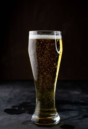 selective focus, glass of light bottle beer with foam, vertical position