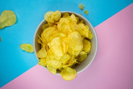potato chips with salt, in a dinnerware, on a colored background