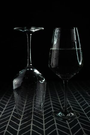 selective focus, transparent wine glasses with water in a counter light with highlights on a dark background