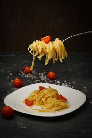 Italian pasta on a plate on a dark background with cherry tomatoes Zdjęcie Seryjne