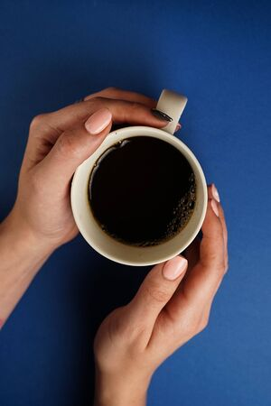 selective focus, female hands holding a mug of black tea on a blue background Reklamní fotografie