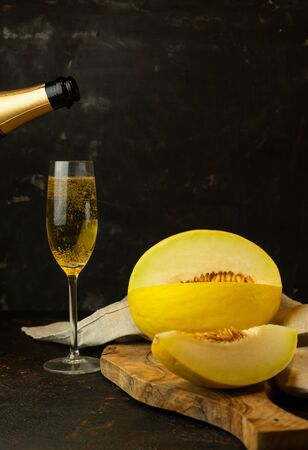 juicy yellow small melon with a glass of champagne on the table, on a dark background Stock fotó