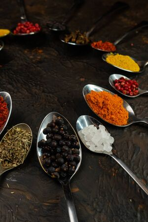 selective focus, copper tablespoons and teaspoons with cooking spices for cooking, on a dark background