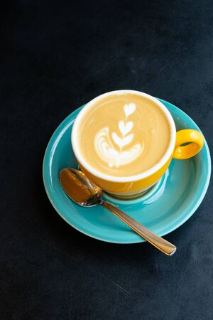 selective focus, a beautiful mug of hot cappuccino with a pattern on a dark blue table