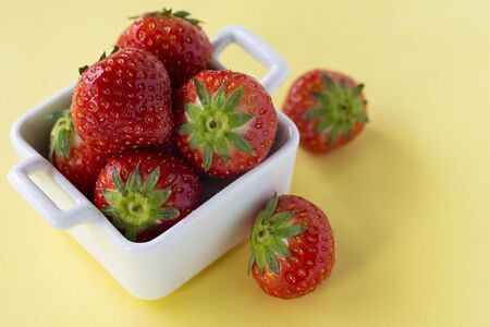 red fresh strawberry berries in white ceramic dishes on a colored background, copyspace