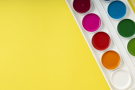 clean new palette of watercolors on a yellow paper background, copyspace