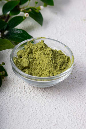 green powder of Chinese matcha tea on a white light background. vertical position