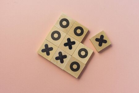 selective focus, wooden dice game TIC-TAC-toe on a paper colored background, copyspace