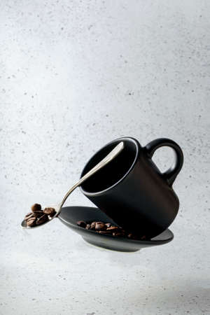 selective focus, flying espresso mug, with saucer and coffee beans on a light background