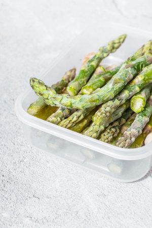 frozen green asparagus pods in a containe Banco de Imagens