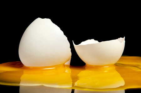 Broken raw egg yolk with a great close-up on a black background photo