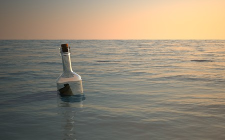 message: Bottle message floating around in calm ocean Stock Photo