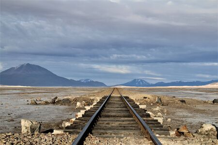 Railroad at the borders of Bolivia and Chile going nowhere in the middle of desert. Where old trains used to pass, now abandoned. Feeling lost? Do not follow this road. 스톡 콘텐츠