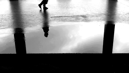 man reflected in a puddle