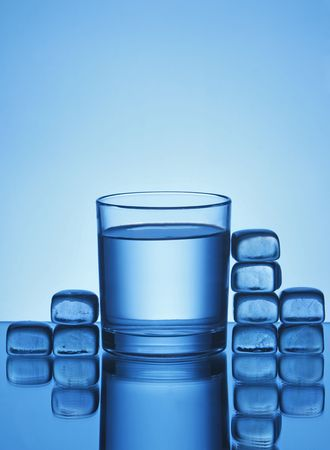 glass of water and ice cubes on blue background photo