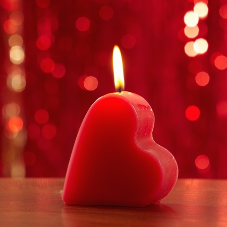 red burning heart shaped candle