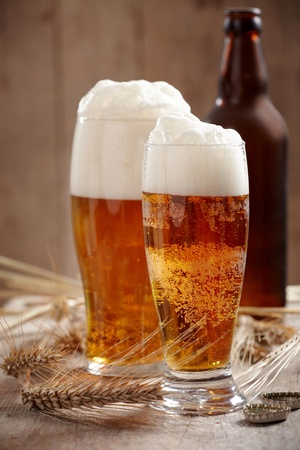 two glasses of beer on old wooden table photo