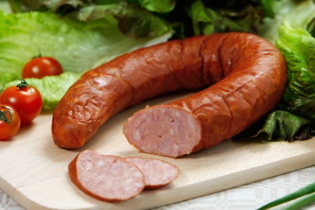 cooked sausage: smoked sausage on wooden cutting board Stock Photo