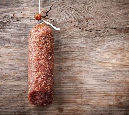air dried salami: hanging salami sausage on wooden background