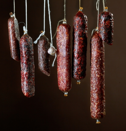 various hanging salami sausages photo