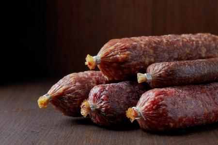air dried salami: various salami sausages on dark brown table Stock Photo