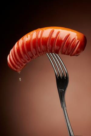 chorizos asados: Salchicha a la parrilla en un tenedor Foto de archivo