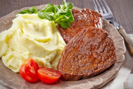 Mashed potatoes and beef steak on plate photo