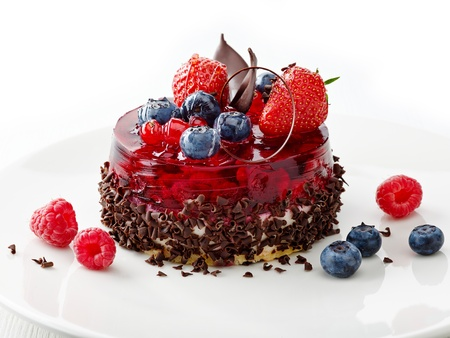 cake with fresh berries and chocolate on white plate photo