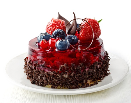 cake with fresh berries and chocolate on white plate