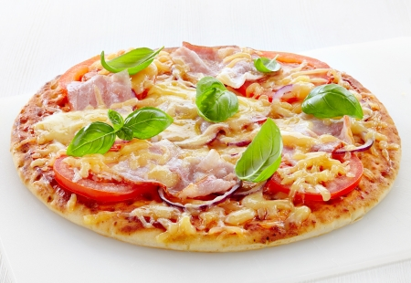 italian cuisine: Pizza with bacon and tomato on white cutting board Stock Photo