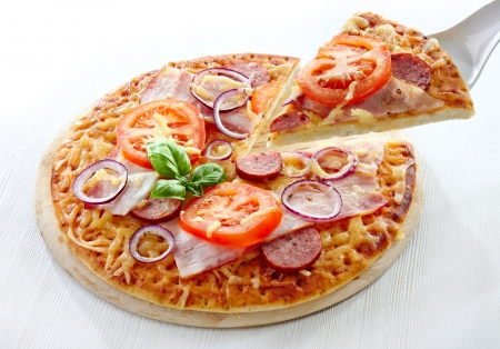 Salami and tomato pizza on wooden cutting board photo
