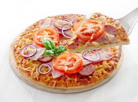 Salami and tomato pizza on white wooden table photo