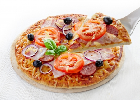 Pizza with salami, bacon, tomato and black olives on white wooden table photo