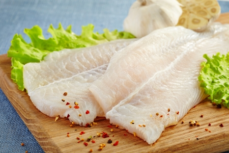 bream fish: fresh raw pangasius fish fillet on wooden cutting board Stock Photo