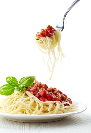 Spaghetti bolognese and green basil leaf on white plate photo