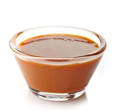 caramelo: salsa dulce de caramelo sobre un fondo blanco Foto de archivo