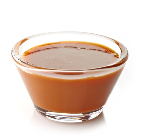 dulce de leche: salsa dulce de caramelo sobre un fondo blanco Foto de archivo