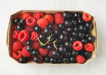 fresh raspberries and black currant berries in a box photo