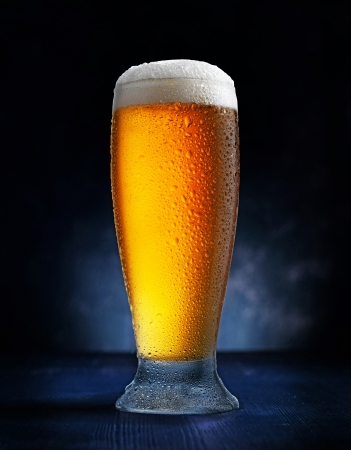 pint glass: glass of beer on dark blue background