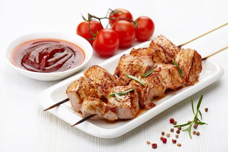 meat skewers: grilled pork meat on white plate