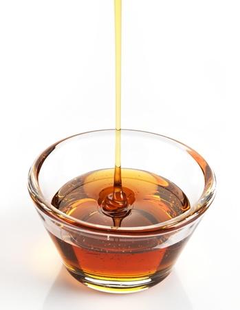 jarabe: El jarabe de arce en un recipiente en el fondo blanco
