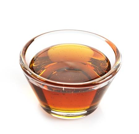 in syrup: El jarabe de arce en un recipiente en el fondo blanco