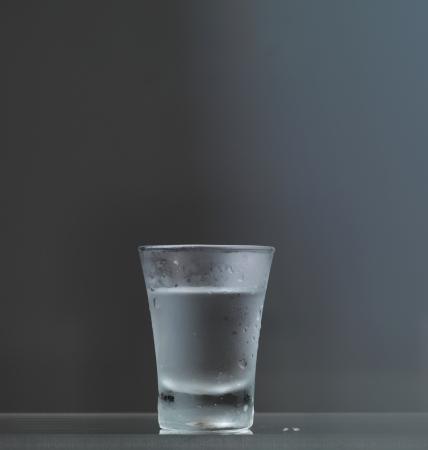 Cold vodka glass on grey background photo