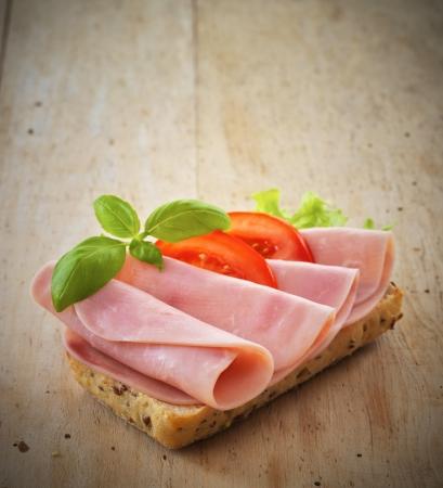 sandwich with pork ham and tomatoes Фото со стока