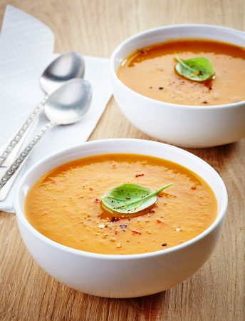 butternut: two bowls of squash soup on wooden table